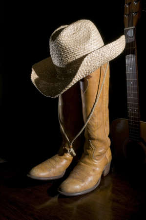 Spotlight on Cowboy Boots with acoustic guitar in the background Stock Photo