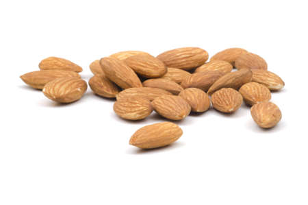 Multiple almonds on a white background with the focus on the foreground almonde Stock Photo