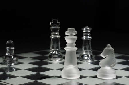 Kings facing each other with one with selective focus and the other in the background, Queen and Knight on the board