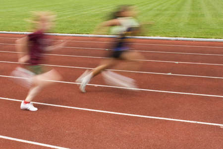 Blurred motion of two females racing on the track photo