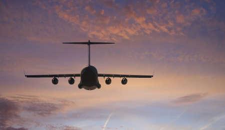 Military transport plane towards the brilliant sunset
