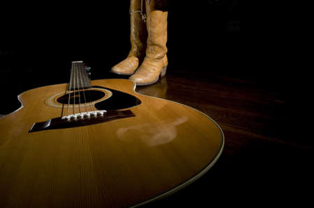Selective focus on the guitar in the foreground with cowboy boots in the background under the spotlight photo