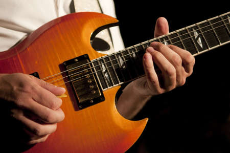 Close up on the hands of a guitar player with copy space in the background Stock Photo - 17944501
