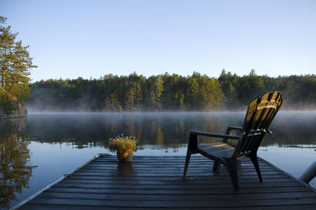 adirondack chair: Morning view of the bay from the dock at Weslemkoon lake Stock Photo