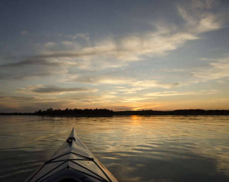 Kayak on the lake with the treeline and sunset in the background