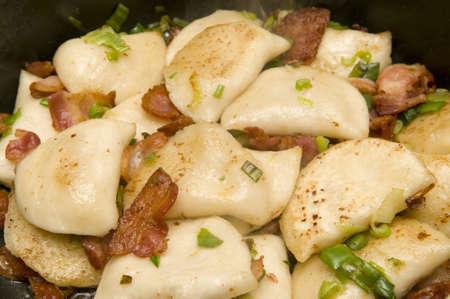 Omwikkeld aardappel met spek en groene uien met selectieve focus op de voorgrond