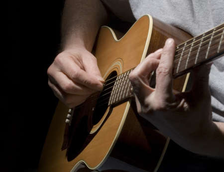 Closeup of guitar and muscians hands with a black background. Stock Photo