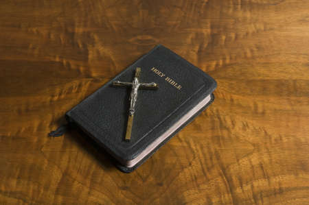 representations: Cross and bible on an antique wood table top. Stock Photo