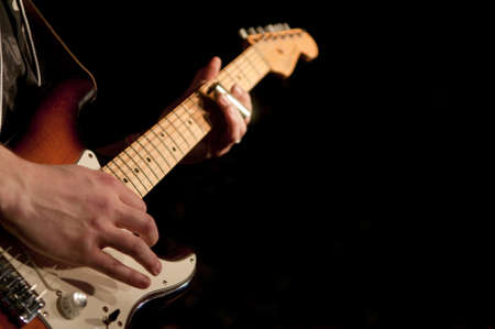 Close up on the hands of a guitar player with copy space in the background Stock Photo - 18172340