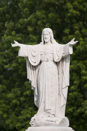 Selective focus on the marble statue of Jesus Christ with tree in the background Stock Photo