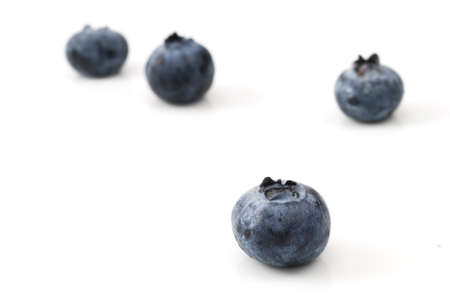 Selective focus on the single blueberry on white background