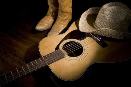 krajina: Zaostřeno na zemi kytaru, boty a klobouk Reklamní fotografie