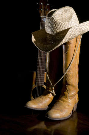 Spotlight on country music symbols, cowboy boots, acoustic guitar and hat Stock Photo - 18355871