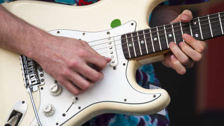 Closeup of a electric guitar and musician picks out some slick riffs Stock Photo