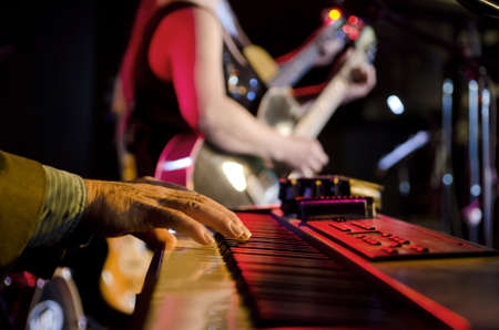 Selective focus on the hands on the keyboard at a blues festival with guitar players in the background photo