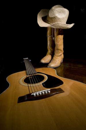 Spotlight op gitaar op de voorgrond met selectieve focus en cowboylaarzen op de achtergrond Stockfoto