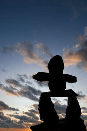 Selective focus on the Inukshuk silhouette in the foreground with sunset in the background