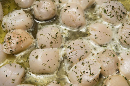 Selective focus on the foreground scallops cooking in butter