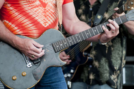 Two rock and rollers at a music festival with selective focus on the forground hands strumming the guitar Stock Photo - 18483403