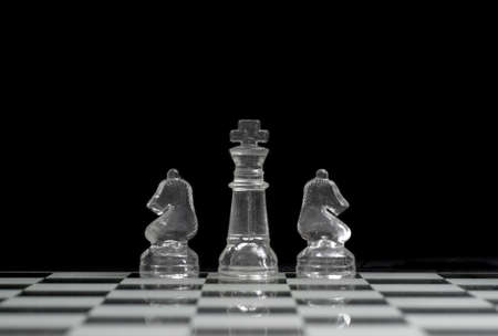 King and two Knights on the chess board with a black background photo