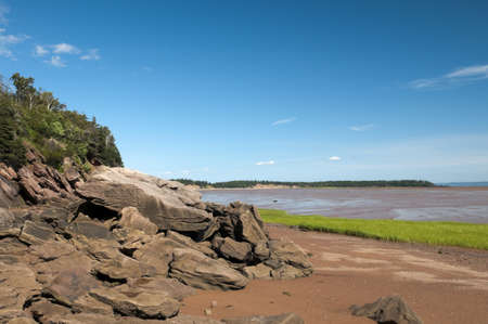 Bay of Fundy shoreline with the tide out and lots of red soil and boulders Stock Photo - 18854159