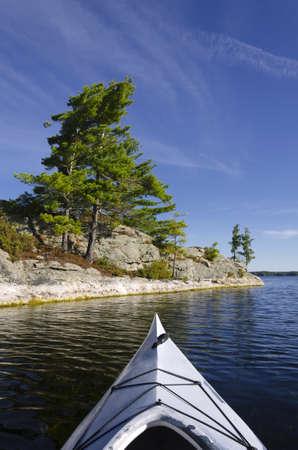 kayaker: Kayak on a northern lake with pine trees on the island
