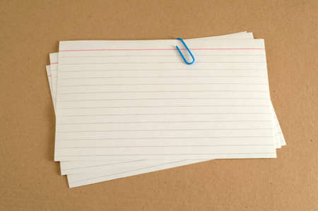 Paper clip holding three index cards sitting on manila folder