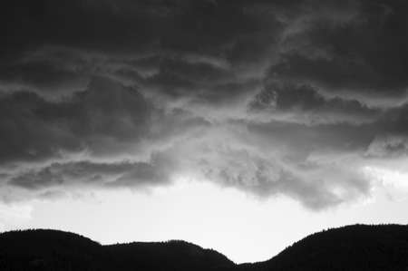 Silhouette of the mountain treeline with storm clouds above. photo