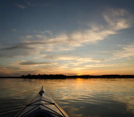 Kayak on the lake with the treeline and sunset in the background   photo