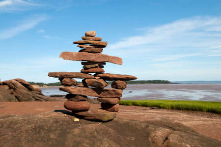inukshuk: Selective focus on the welcoming Inukshuk in the foreground and Bay of Fundy shoreline in the background Stock Photo