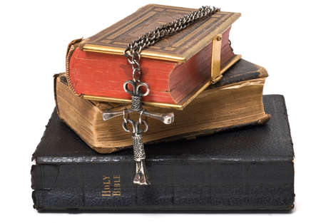 catholicism: Three antique bibles with a nail cross hanging off the edge