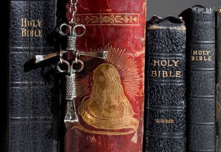 Spine view of multiple bibles with the nail cross hanging in the front.