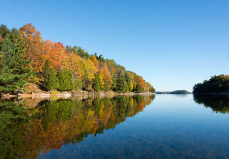 Sunny day in autumn on a northern lake with fall colours on the forest reflecting on the lake