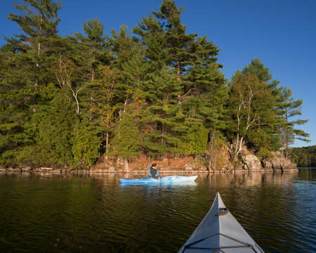 Woman kayaking in autumn on a northern lake with vibrant colors and great reflections on the tranquil lake