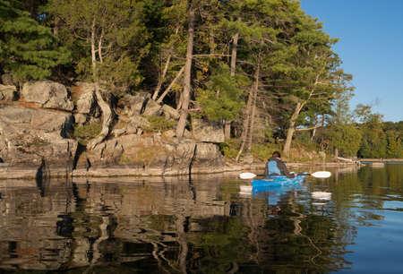 Vrouw kajakken in de herfst op een noordelijk meer met levendige kleuren en grote reflecties op het rustige meer