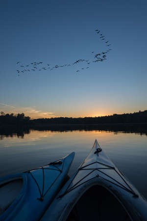 Geese flying over the northern lake at sunset looking to land with two kayaks in the foreground