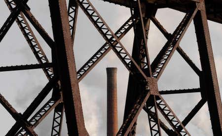 Oude trein brug op de voorgrond met een fabriek schoorsteen spuwen vervuiling in de lucht