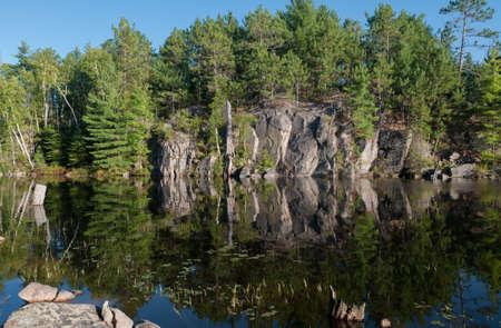 Northern meer met een rotswand relection in een kleine rustige baai