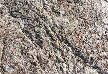 Close-up van een kant van een granieten rots met contrast in de grove textuur. Stockfoto