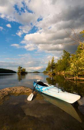 Kayak on sunlight shoreline on a northern lake