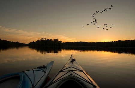 Twee kajaks op het meer met ganzen op zoek naar land bij zonsondergang Stockfoto