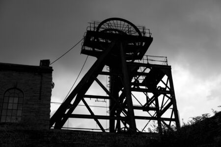 stark: Old abandoned Welsh Coal Mine Pit Gear Silhouette, stormy sky Stock Photo