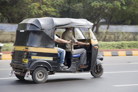 three wheeler: Auto rickshaw transport with driver and passenger on the road in Mumbai, India Editorial