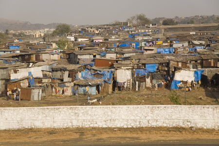 shanty: Shanty town in Mumbai viewed from a taxiing aircraft at airport- marked contrasts Stock Photo