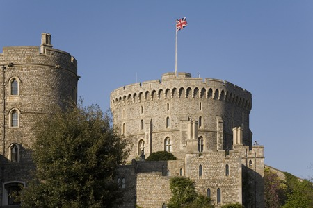 View of Windsor Castle from outside of grounds - tower and british flag Editorial