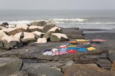 evaporate: Laundry day in Mumbai - washing drying on the coastal rocks
