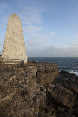 obelisk stone: Stone obelisk on rocks by sea at Portland Bill, England