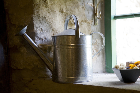 side lighting: Galvanised steel watering can on windowsill lit from outside Stock Photo
