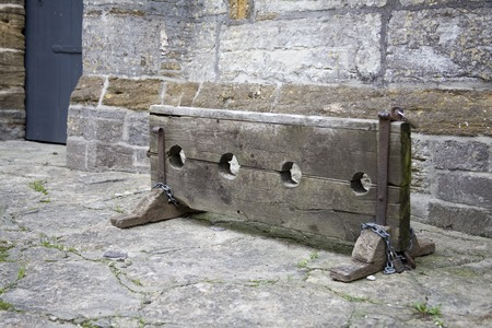 english village: Wooden stocks - traditional punishment for crime in English village