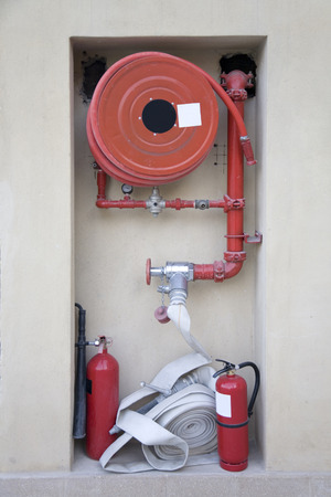 fire extinguishers: Firefighting equipement - hose reel and fire extinguishers at an underground car park Stock Photo